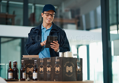 Buy stock photo Cropped shot of a handsome young man taking inventory of items that he has to deliver to customers
