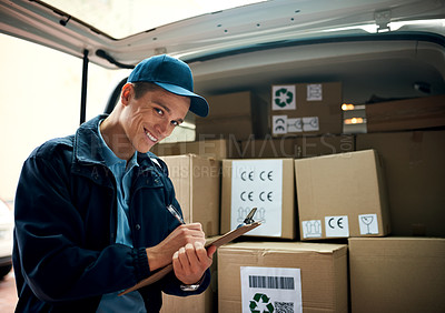 Buy stock photo Cropped shot of a handsome young delivery man using a clipboard
