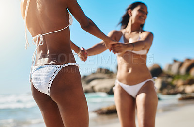 Buy stock photo Shot of two young women enjoying a playful moment on the beach