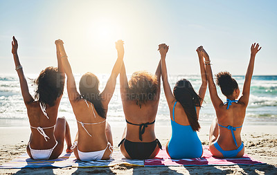 Buy stock photo Rearview shot of a group of happy and relaxed young women raising their hands together at the beach