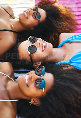 Buy stock photo Shot of a group of happy young women wearing sunglasses and relaxing at the beach