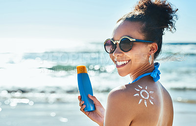 Buy stock photo Portrait of a beautiful young woman with a sun drawn on her shoulder with sunscreen at the beach