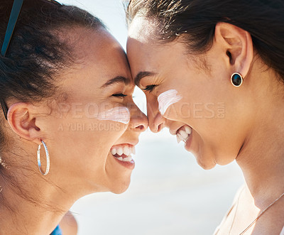 Buy stock photo Shot of two beautiful young women at the beach with sunscreen on their faces smiling at each other