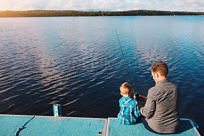 Buy stock photo Shot of a father and his young son out fishing by the lake