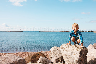Buy stock photo Shot of an adorable little boy playing on the rocks