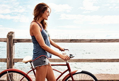 Buy stock photo Cropped shot of a beautiful young woman with her bicycle on the promenade