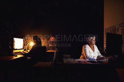 Buy stock photo Shot of two businesswomen working late in an office