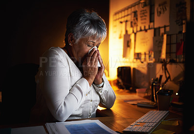 Buy stock photo Shot of a mature businesswoman blowing her nose while working late in an office