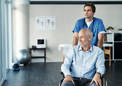 Buy stock photo Shot of a male nurse caring for a senior patient in a wheelchair