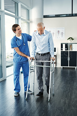 Buy stock photo Shot of a male nurse assisting a senior patient with a walker