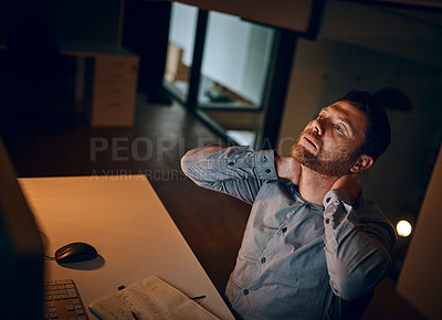 Buy stock photo Shot of a young businessman suffering with neck pain while working late in an office