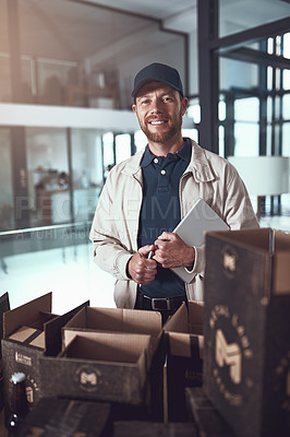Buy stock photo Portrait of a cheerful young man packing boxes on top of each other inside of a office building during the day