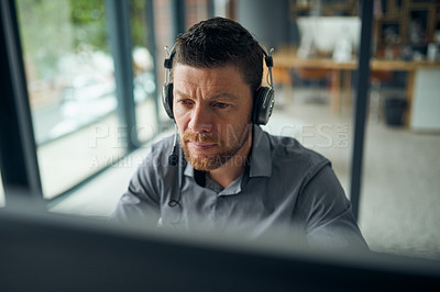 Buy stock photo Shot of a mature man working on a computer in a call centre