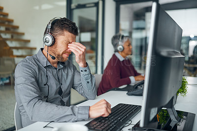 Buy stock photo Shot of a mature man looking stressed out while working on a computer in a call centre