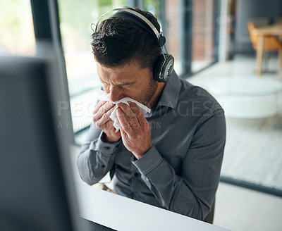 Buy stock photo Shot of a mature man blowing his nose while working on a computer in a call centre