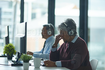 Buy stock photo Shot of a mature woman looking stressed out while working on a computer in a call centre