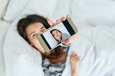 Buy stock photo Shot of an attractive young woman taking a self portrait with her cellphone while lying in bed at home