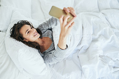 Buy stock photo Shot of an attractive young woman typing on her cellphone while lying in bed at home during the day