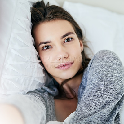 Buy stock photo Portrait of an attractive young woman taking a self portrait with her cellphone while lying in bed at home