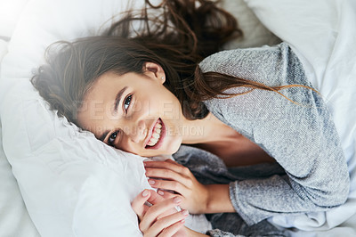Buy stock photo Portrait of an attractive young woman lying bed while smiling brightly at home during the day