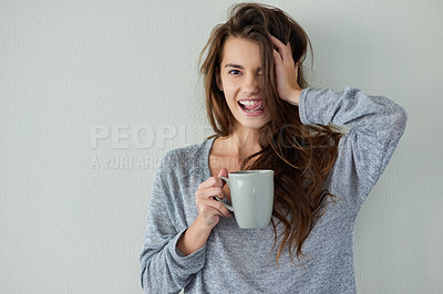 Buy stock photo Studio shot of an attractive young woman holding the side of her head while drinking coffee against a white background