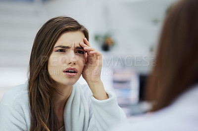Buy stock photo Shot of a confused looking young woman looking into a mirror with her hand touching her face at home during the day