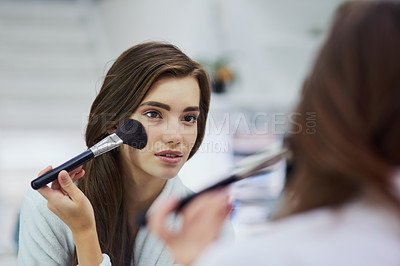 Buy stock photo Shot of an attractive young woman looking into a mirror while applying makeup to her face at home during the day