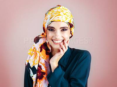 Buy stock photo Studio portrait of a cheerful young woman wearing a colorful head scarf while posing against a pink background