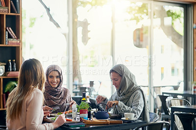Buy stock photo Shot of a group of women getting together for lunch in a cafe