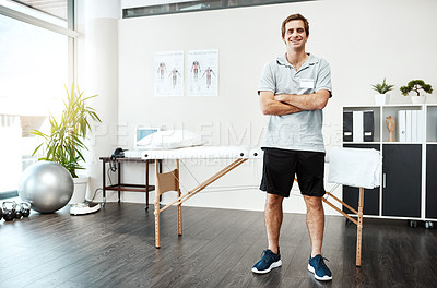 Buy stock photo Portrait of a confident young male physiotherapist standing with his arms folded inside of his office