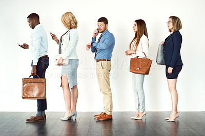 Buy stock photo Studio shot of a group o focused people standing in row behind each other against a white background