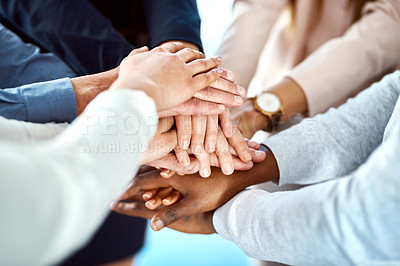 Buy stock photo Shot of a group of unrecognizable people forming a huddle with their hands inside of the office during the day