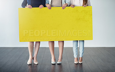 Buy stock photo Cropped studio shot of a group of businesswomen holding up a blank yellow placard