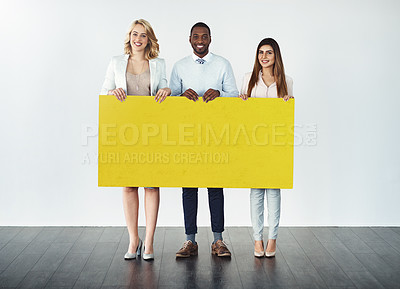 Buy stock photo Studio shot of a group of businesspeople holding up a blank yellow placard