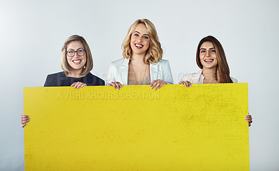 Buy stock photo Studio shot of a group of businesswomen holding up a blank yellow placard