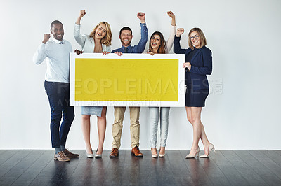 Buy stock photo Studio shot of a group of businesspeople holding up a blank yellow placard and cheering