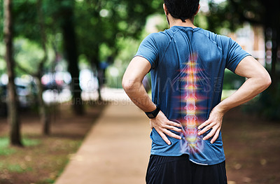 Buy stock photo Rear view shot of a sporty young man holding his back in pain while exercising outdoors