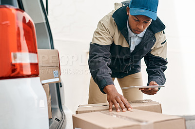 Buy stock photo Shot of a courier using a digital tablet while sorting boxes from a delivery van