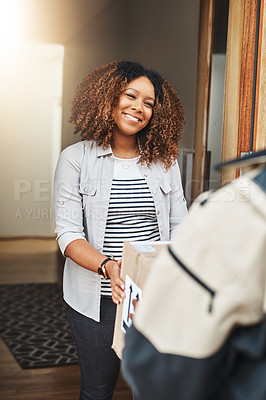 Buy stock photo Shot of a young woman receiving a delivery from the courier