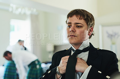 Buy stock photo Shot of a confident young man folding a tie while looking into a mirror to get ready for a wedding