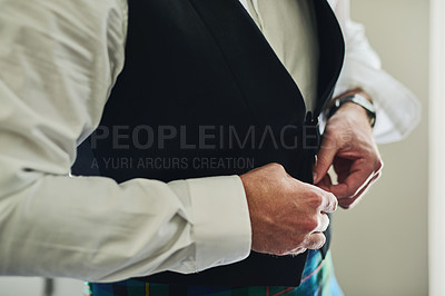 Buy stock photo Shot of an unrecognizable man putting on formal clothes to get ready for a wedding inside of a building during the day