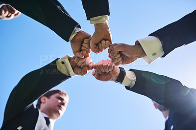 Buy stock photo Low angle shot of a group of well dressed men forming a huddle and giving each other a fist pump outside during the day