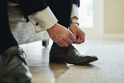 Buy stock photo Shot of a unrecognizable man's hands tying the laces on a pair of formal shoes inside a building during the day