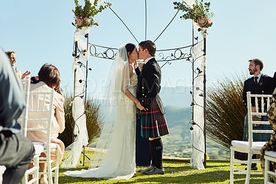 Buy stock photo Shot of a cheerful young bride and groom sharing a kiss at a wedding alter to signify that they are officially married