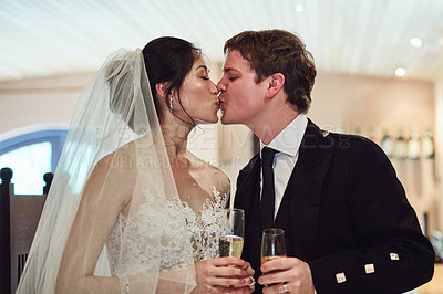 Buy stock photo Shot of a cheerful young bride and groom sharing a kiss with each holding a champagne glass inside of a building