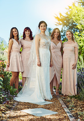 Buy stock photo Portrait of a cheerful young bride and her bride's maids standing together outside during the day