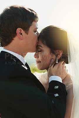 Buy stock photo Shot of a cheerful young groom giving his bride a kiss on the forehead while they stand holding each other outside