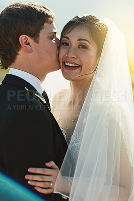 Buy stock photo Portrait of a cheerful young groom giving his bride a kiss on the cheek while they stand holding each other outside
