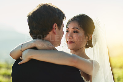 Buy stock photo Shot of a cheerful young bride and groom holding each other while looking eye to eye outside during the day