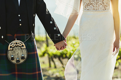 Buy stock photo Shot of an unrecognizable bride and groom holding hands and walking together outside during the day